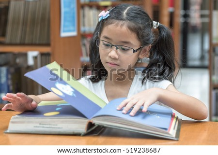 Happy little asian child girl wear eyeglasses reading book school background: Lovely cute young student kid opening flipping book in archive resource collection room: National library lover month week