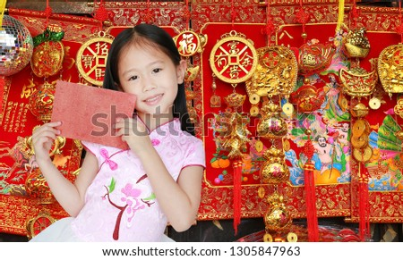 45e724fec Happy little Asian child girl wearing pink traditional cheongsam dress  smiling while receiving red envelope packet