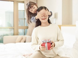 happy little asian girl giving mother a gift and covering mother's eyes with hands
