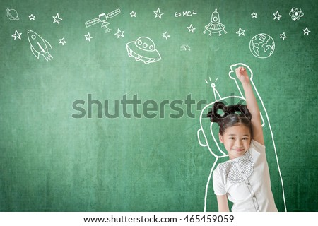 Happy little asian girl kid in astronaut suit doodle chalk board drawing out of earth planet on school green chalkboard background for World UFO day and outer space week education concept idea