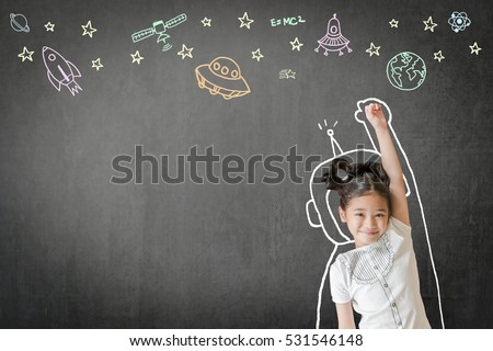 Happy little asian girl kid in astronaut suit doodle chalk board drawing out of earth planet on school black chalkboard background for World UFO day and outer space week education concept idea