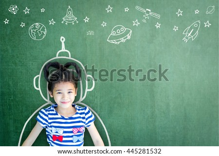 Happy little asian girl kid in astronaut suit doodle chalk board drawing universe out of earth planet school green chalkboard background: World UFO outer space week creative education concept idea