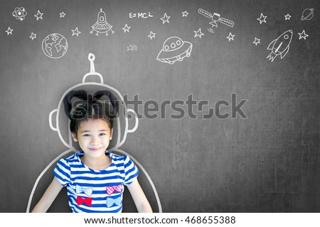 Happy little asian girl kid in astronaut suit doodle chalk board drawing & universe space out of earth planet on school black chalkboard background: Creative innovation educational conceptual idea