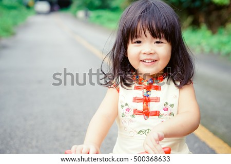 Happy Little Asian Girl On A Bicycle Caught In Motion On A Driveway