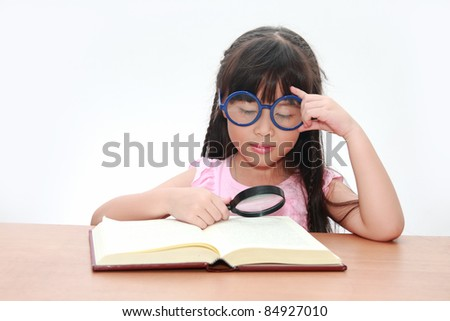 Happy little asian girl reading book wearing blue glasses, back to school concept, isolated over white