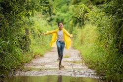 happy little asian  girl running and jumping in puddles after rain in summer. child play in autumn rain. kid playing on the nature outdoors. girl is wearing yellow raincoat and enjoying rainfall.