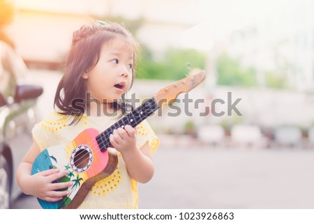 Happy little asian girl sing a song playing ukulele on street.