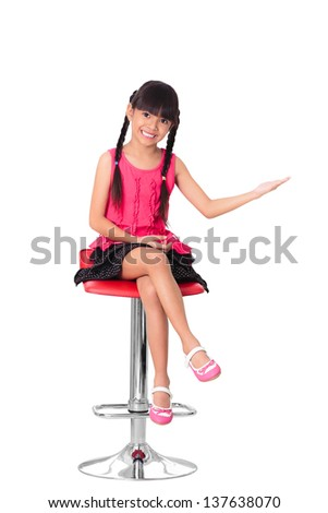 Happy little asian girl sitting on high chair, Isolated over white with clipping path