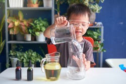 Happy little Asian school kid studying science, making DIY Lava Lamp Science Experiment with oil, water and food coloring, Kid-friendly fun and easy science experiments at home concept