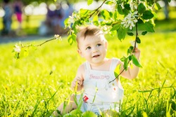 happy little baby boy sitting on a green meadow on the nature in the park