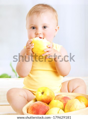 Happy little baby girl eating fresh tasty fruits for lunch, enjoying healthy food at home, organic nutrition for kids