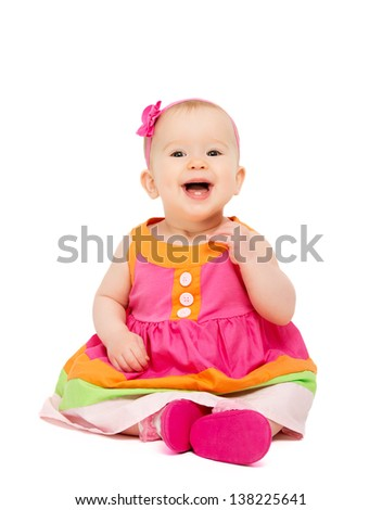 happy little baby girl in bright multicolored festive dress isolated on a white background