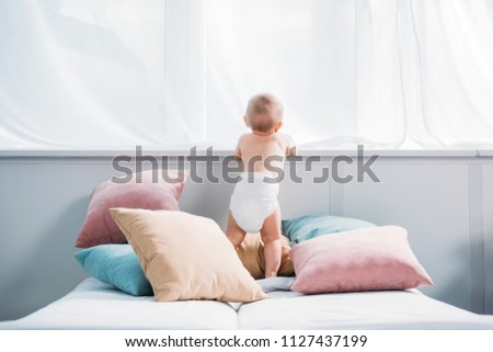 happy little baby in diaper standing on bed with lot of pillows and looking through window