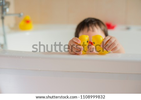 Happy little baby in the bathroom playing with rubber yellow dots. Infant training and bathing. Hygiene and care for young children. Сток-фото ©