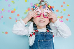 Happy little blonde girl pressing happy birthday glasses to her face, wearing jeans overalls lies on a blue-surfaced floor with colorful confetti pieces over her head. Top view. Funny face.