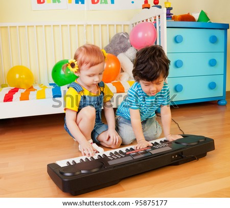 Happy little boy and girl playing a musical instrument