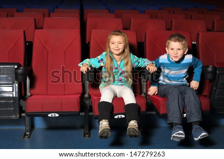Happy little boy and girl together watching a movie