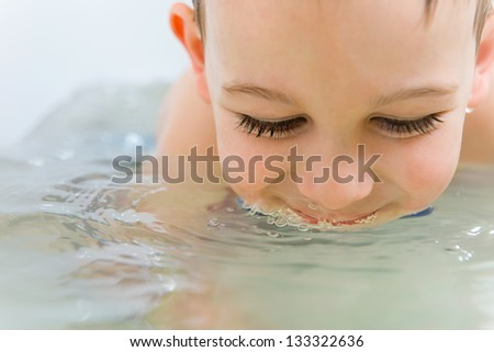 Happy little boy bathing in bathtub at home