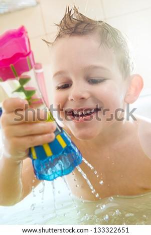 Happy little boy bathing in bathtub at home