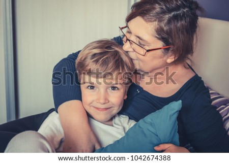 Happy little boy being kissed by his grandmother.  #1042674388