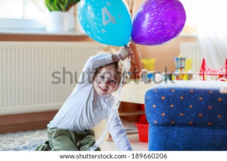 Happy little boy celebrating his 4 birthday with colorful balloons, indoor in kids room.