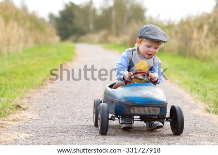 happy little boy driving big...