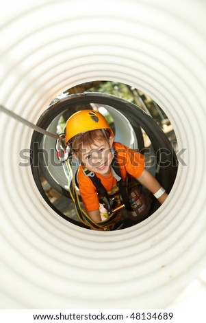 Happy little boy having fun in adventure park crawling in tube wearing mountain helmet and safety equipment.