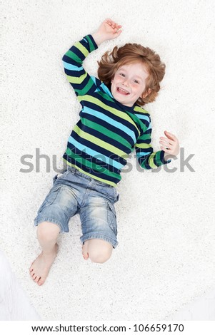Happy little boy having fun laughing on the floor - top view