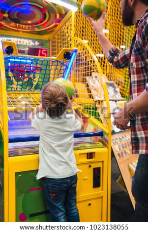 Happy little boy having fun with his dad at the entertainment centre