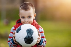Happy little boy holding ball outdoors.Photo of smiling little boy holding soccer ball.Happiness and fun concept.