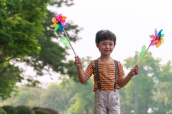 Happy little boy holding windmill in his hands while standing with tree in morning at the public park. Child cute boy playing pinwheel while walking find windy at garden park.