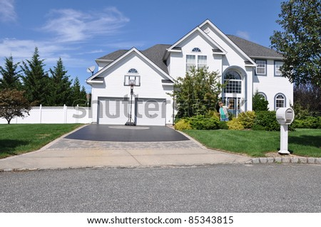 Happy Little Boy in Front Yard of Large Two Car Garage Suburban Residential District Home on Sunny Blue Sky Day