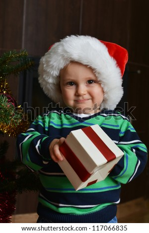 happy little boy in santa cap with  christmas gift