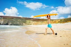 Happy little boy in shorts run with orange surfboard on the hand to the sea waves on the beach side view