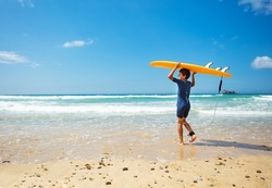 Happy little boy in swimsuit walk into sea waves with orange surfboard on the hand on the beach back view