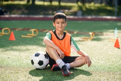 Happy little boy in uniform sitting on soccer field with a ball in front of him after training.