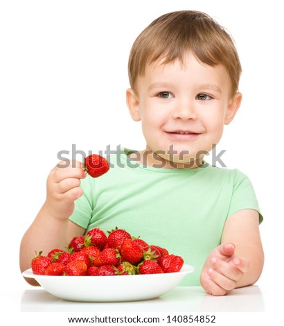 Happy little boy is eating strawberries, isolated over white