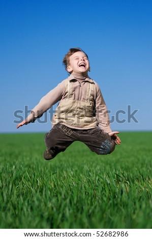 Happy little boy jumping in field against blue sky
