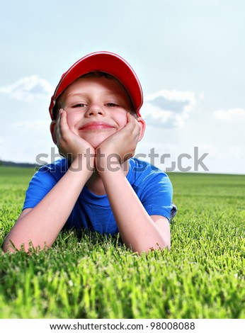 happy little boy laying on  grass