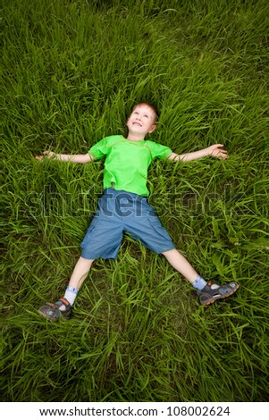 happy little boy laying on the green grass - stock photo