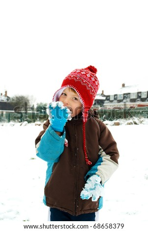 happy little boy licking snow off his gloves