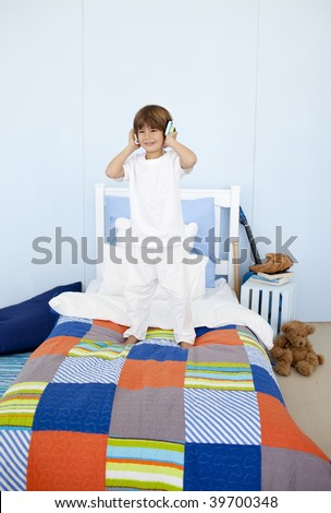 Happy little boy listening to music and dancing in bedroom