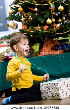 Happy little boy opening Chrismas present at Christmas Eve under the Christmas tree.