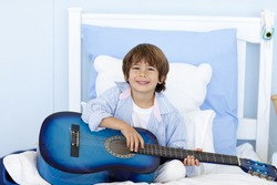 Happy little boy playing guitar sitting in bed