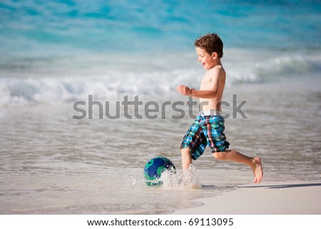 Happy little boy playing with ball on tropical beach
