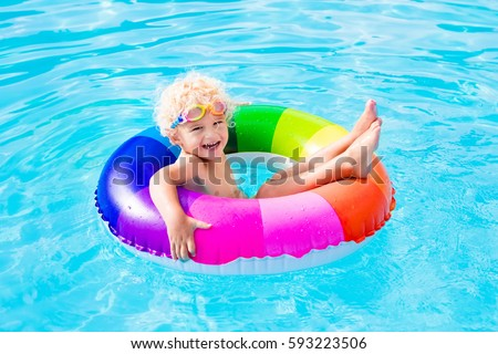Happy little boy playing with colorful inflatable ring in outdoor swimming pool on hot summer day. Kids learn to swim. Child water toys. Children play in tropical resort. Family beach vacation.