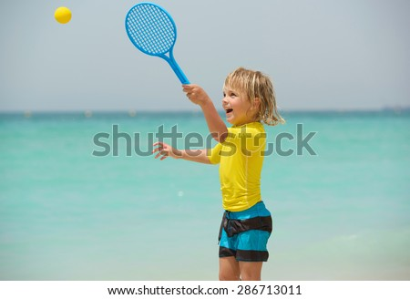 Happy little boy plays beach tennis and has fun on summer vacation