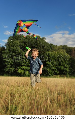 Happy little boy running with bright colors kite at the field