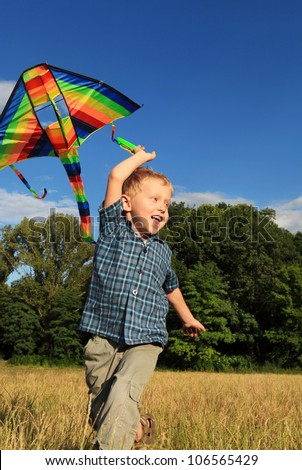 Happy little boy running with bright kite over his head