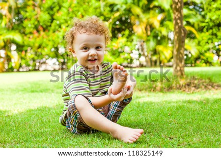 happy little boy sitting on the grass in the garden
